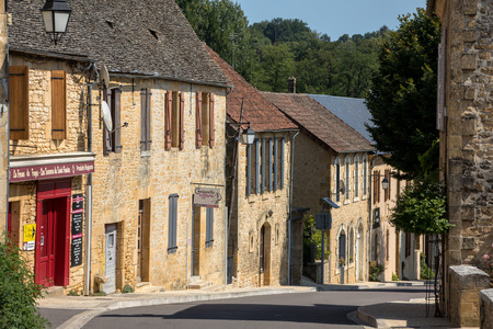 Saint Genies, France - September 2, 2018:  Saint Genies is a lovely; village between Montignac and Sarlat. At the centre of the village is a beautiful ensemble consisting of the church of Notre Dame de l'Assomption and the castle. Perigord; Dordogne; Fran