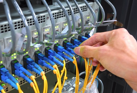hand with fiber cables connected to servers in a datacenter