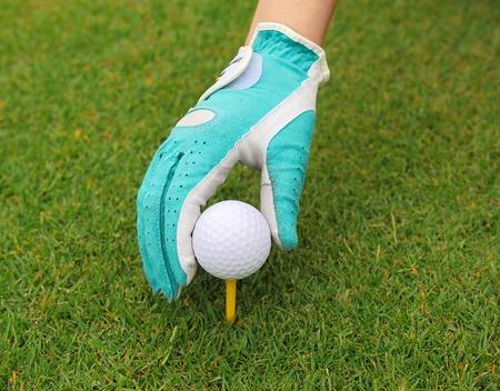 gloved hand putting a golf ball on a tee