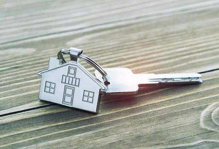 Foto de keychain with house symbol and keys on wooden background,Real estate concept - Imagen libre de derechos
