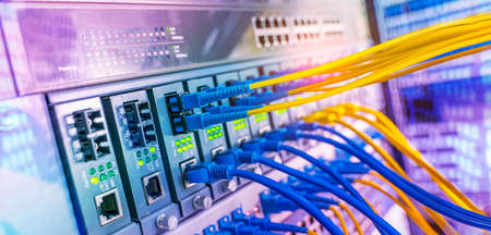Photo pour Fiber Optical cables connected to an optic ports and Network cables connected to ethernet ports - image libre de droit
