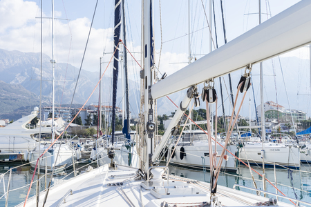 Bar, Montenegro, February 08, 2019: Close-up view from the deck of the yacht to the marina with moored boats and yachts and the bow of the yacht with folded sail