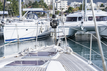 Bar, Montenegro, February 08, 2019: View from the deck of the yacht to the marina with moored boats and yachts and close-up the bow of the yacht