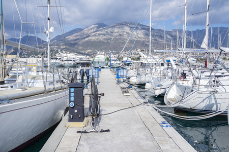 Bar, Montenegro, February 08, 2019: Marina of Bar town in a bright sunny day. View of the yacht's jetty with moored white yachts and motorboats in a row. Mountains in the background