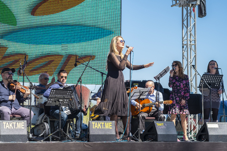 Virpazar, Montenegro, March, 24, 2019: Public festivity of wine and fish in the Montenegrin town Virpazar. In the park on the stage in the open air, a local band performs - violinist, guitarist, accordionist, vocalist and backing vocalists. Woman singer w
