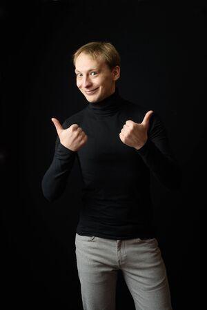 Photo pour Portrait of determined goodlooking man wearing black clothes, black background. - image libre de droit
