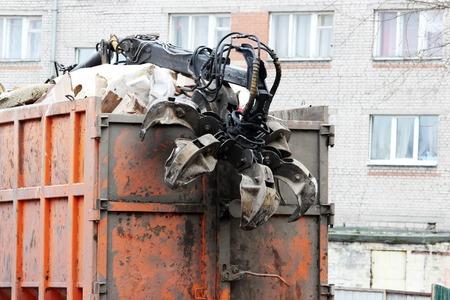 orange garbage truck with manual hydraulic manipulator