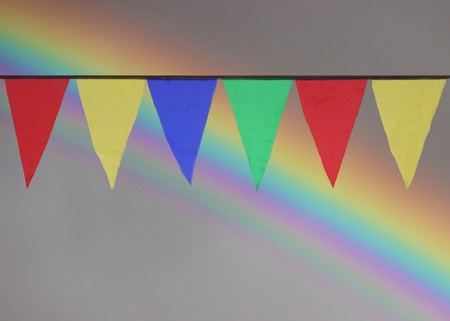 Multi Colored Triangular Flags Hanging in the Sky at an Outdoor against the backdrop of a rainbow