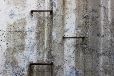 three metal steps on a concrete gray wall lead to the surface of the earth from the tunnel.