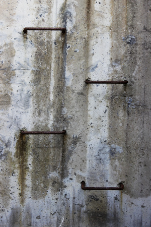 four metal steps on a concrete gray wall lead to the surface of the earth from the tunnel.
