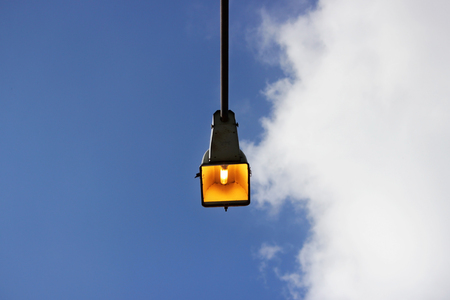 one city lantern on a concrete column lit a summer sunny day against a blue sky
