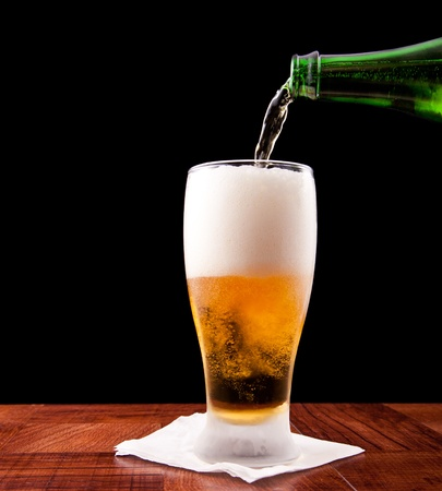 bottle pouring a beer into a chilled glass isolated on a black background