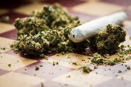 closeup of marijuana joint and buds on a checkerboard table with a shallow depth of field