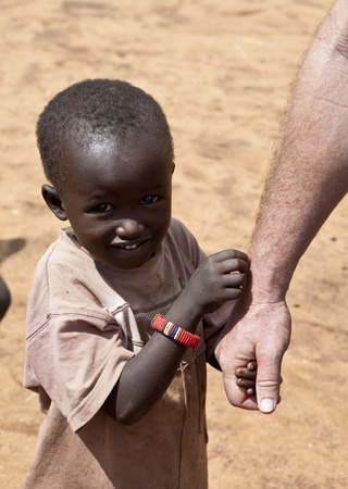 Photo for BISIL, KENYA-DECEMBER 7, 2010: An unidentified Maasai child holds an aid worker's hand near the village of Bisil in southern Kenya - Royalty Free Image