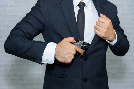 Photo for businessman with gun on gray background - Royalty Free Image