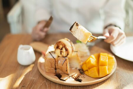 Photo for close up of hand girl eating honey toast on wood table in the cafe - Royalty Free Image