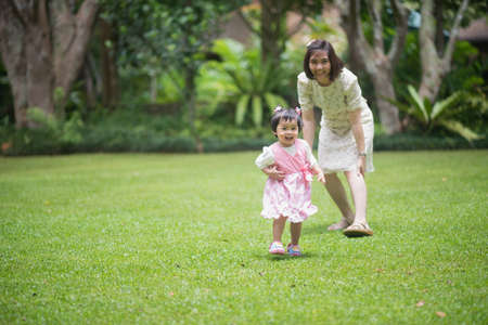 Photo pour cute baby holding hand mom and walking in the garden - image libre de droit