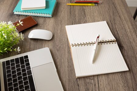 Photo for A  selective shot focus of a business desk includes opening book, a multi-colored pens, books, computer laptop, mouse and flowers on a wooden table to connect with others in the digital technology world with copy space. - Royalty Free Image
