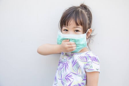 A cute Asian girl, about 3 years old, wearing a face mask to prevent infection during the flu epidemic and dust floating in the air.