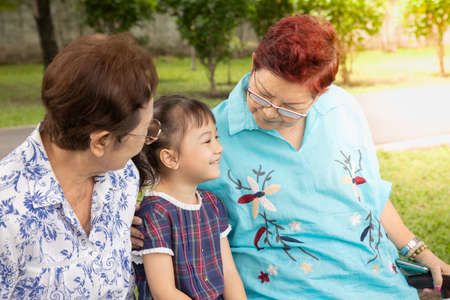 Photo pour Close up family shot of two grandmothers and their adorable granddaughter posing happily in the park outdoor shows positively smiling faces of senior persons having fun with kidin casual style. - image libre de droit