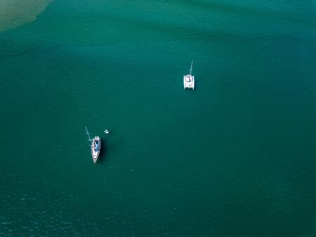 Photo pour A view from a high-angle drone sees sailboats leaving anchors in a beautiful bay, clear glass-like water. - image libre de droit