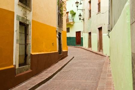 Colorful buildings line a narrow cobblestone street in romantic Guanajuato Mexico