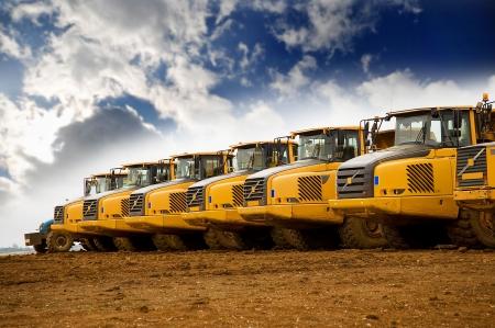 Row of yellow heavy tipper trucks