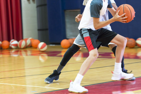 Two teenage male basketball players doing a one on one drill indoors at a local basketball camp over the summer.