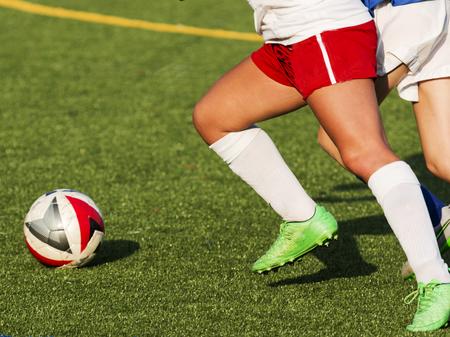 Foto für Two girls chasing a soccer ball during a high school game on a sunny afternoon. - Lizenzfreies Bild