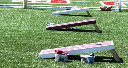 Photo for Three homeaide wooden corn hole game boards are set up side by side on a green turf field with bean bags in containers. - Royalty Free Image