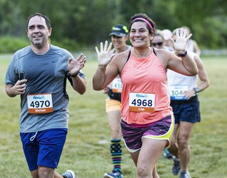 Foto per Kings Park, New York, USA - 17 June 2019: Excited runners waving to camera suring the New York State Parks summer seiries 10K run at Sunken Meadow. - Immagine Royalty Free