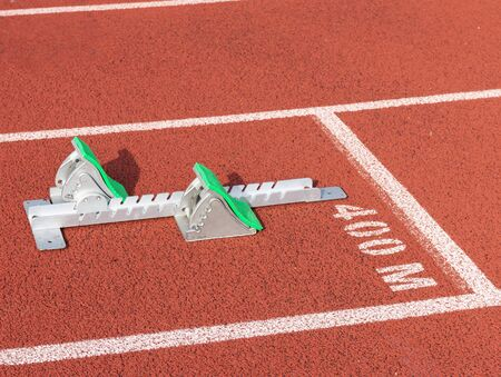 Foto de A set of track and field sprinters starting blocks with green pads, is set up at the start line in lanes of the 400 meter dash. - Imagen libre de derechos