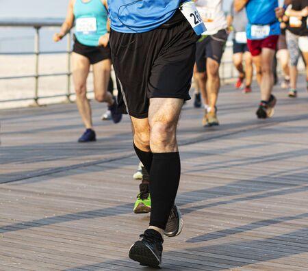 Foto de Runner landing heal to toe while racing a 10K and wearing black compression socks on a boardwalk by the beach. - Imagen libre de derechos
