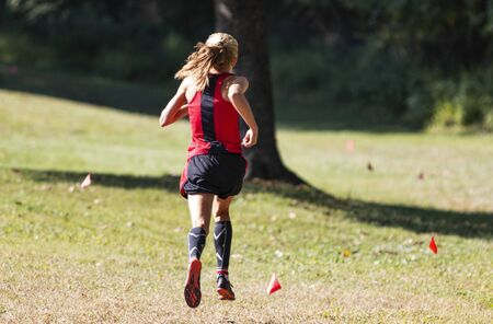 Foto de Rear view of the leader of a girls cross country race following the small red flags marking the course. - Imagen libre de derechos