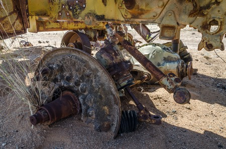 Massive axle of abandoned harvester rusting away deep in the Namib Desert of Angola in detail.