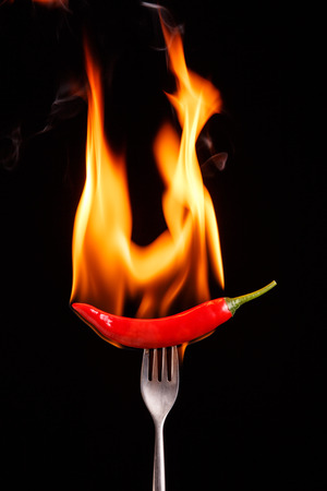 Fork impale to red hot chili on black background.
