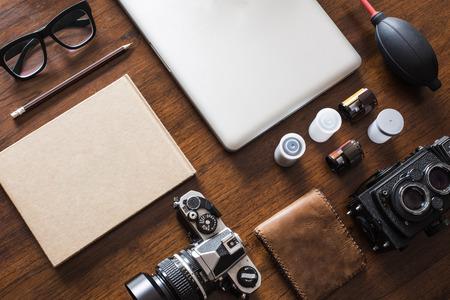Foto de Work space for photographer, designer or hipster style. Have a laptop, film camera, film, speaker, glasses, book, pencil on wooden table. - Imagen libre de derechos