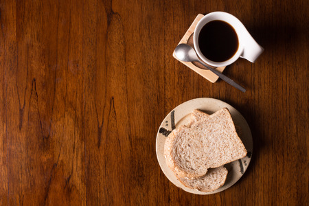 Flat lay of whole wheat bread and and coffee on wooden table.
