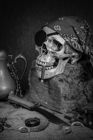 Still life, pirate skull with cigar in the mouth, compass on ancient map, knife and pocket watch hang on the log