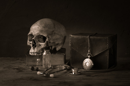 Still life with human skull on old book, stethoscope and pocket watch