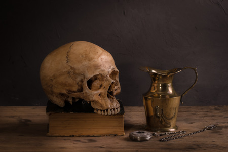 Still life with human skull on old book, vintage brass teapot and pocket watch