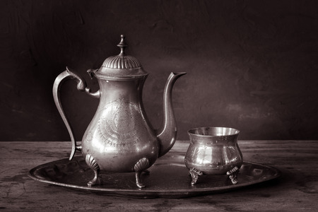 Still life with antique teapot on wooden table