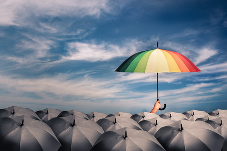 Foto de rainbow umbrella in mass of black umbrellas, concept for creative ideas or leadership and different - Imagen libre de derechos