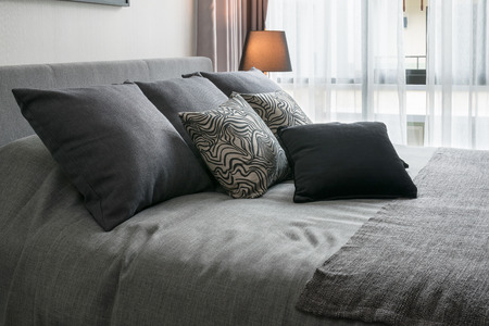 Photo pour stylish bedroom interior design with black patterned pillows on bed and decorative table lamp. - image libre de droit