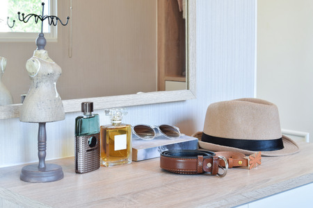 brown hat ,perfume and leather belt on a wooden dressing table