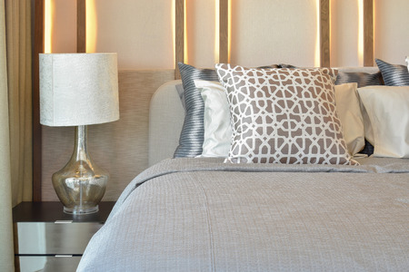 Photo pour stylish bedroom interior design with brown pillows on bed and decorative table lamp. - image libre de droit