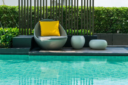 Photo pour Relaxing chairs with pillows beside swimming pool - image libre de droit