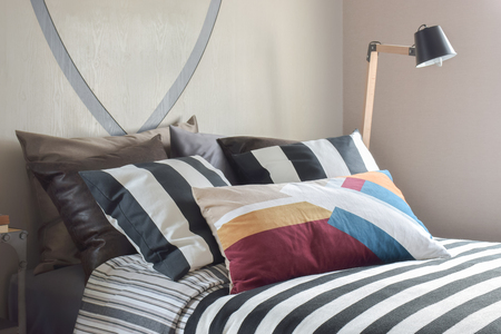 Colorful striped bedding set in light brown bedroom