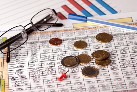 Euro coins arranged on a financial statement with glasses and pen