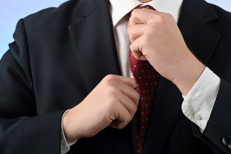 Young businessman in suit adjusting his tie